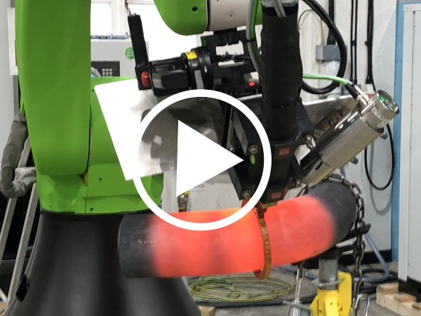 Collaborative robot heating up a pipe to a red hot temperature.